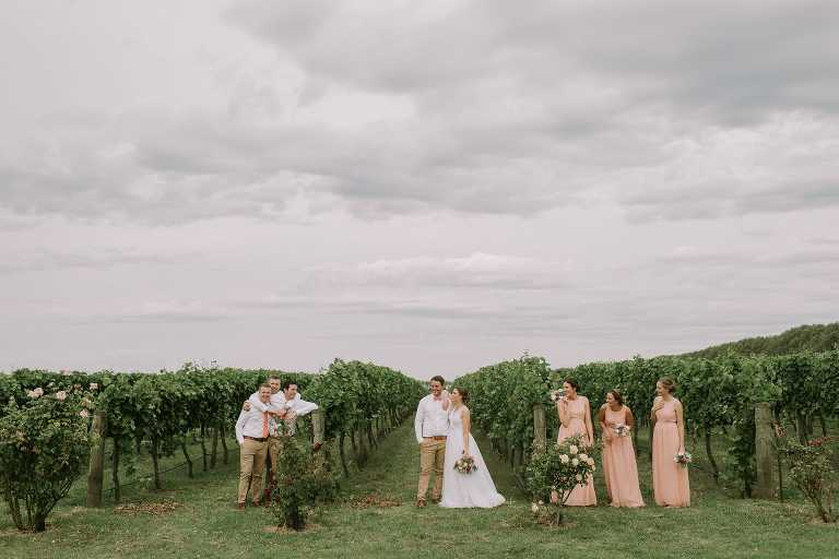 Bridesmaids and groomsmen hanging with Bride and Groom in vineyard at Adelaide wedding photographed by Ivory Fox
