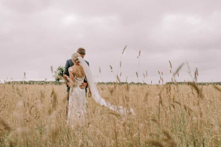 Bride held by groom in gorgeous wheat field at beautiful Adelaide wedding photographed by Ivory Fox
