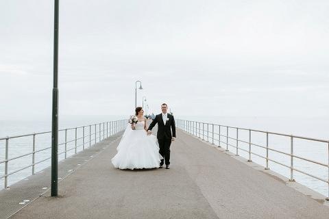 bride and groom walking hand in hand Gelenelg jetty