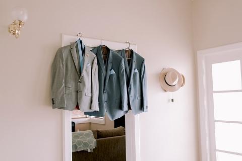 Groom and groomsmen jackets hanging on door