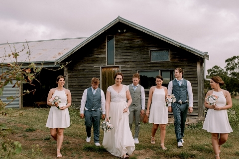 Bridal party walking with barn in background