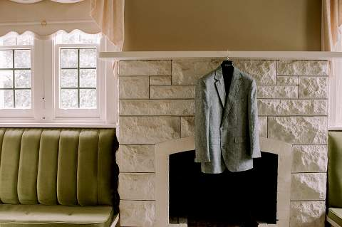 grooms jacket hanging on fireplace